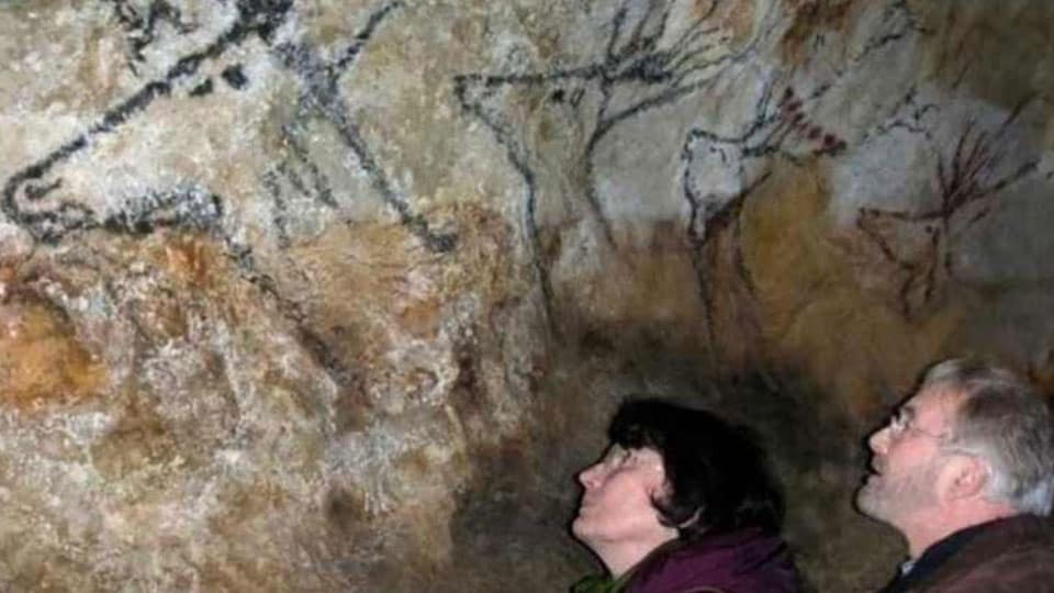 Couple viewing the drawings in Lascaux cave
