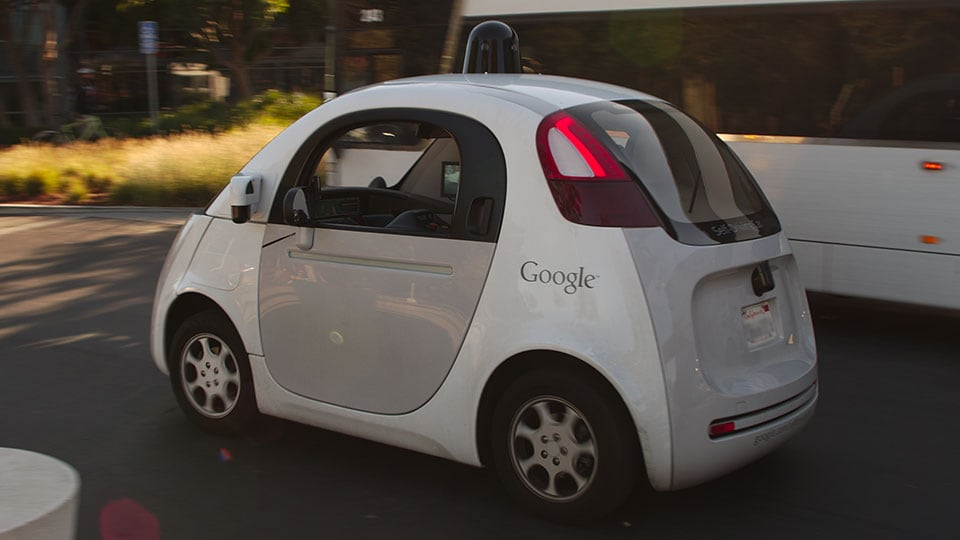 A Google self driving car drives past a double-deck commuter bus at Google's headquarters in Mountain View, CA, USA