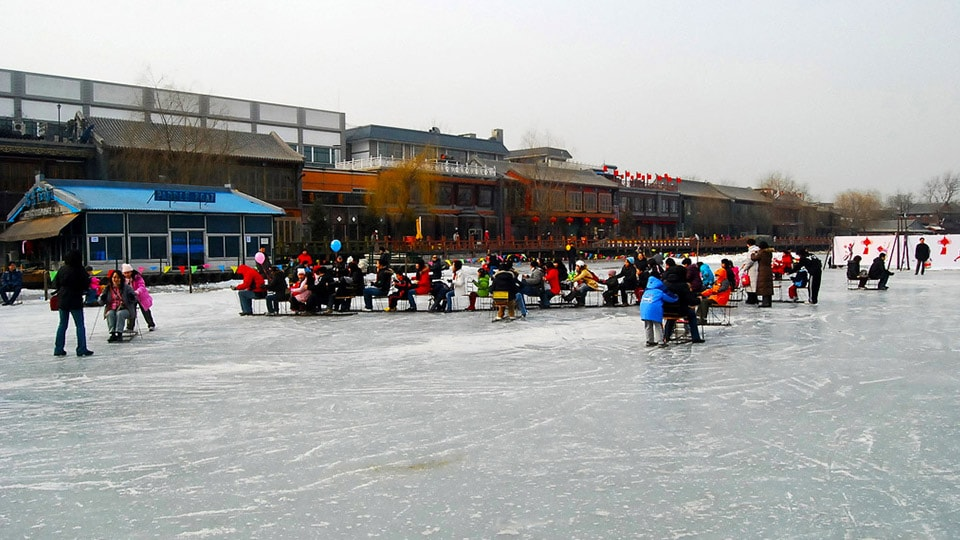 Shichahai, Beijing has groups of people sledging over the frozen lake.