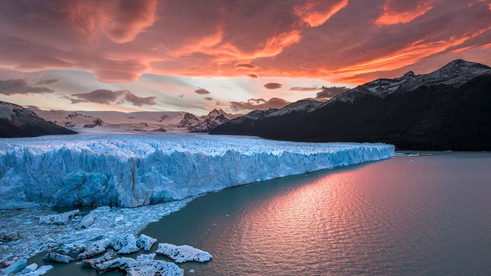 A stunning view of snow-capped mountains, glaciers and an orange sky in Patagonia